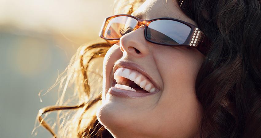 Caucasion woman head tilted back sunshine smiling